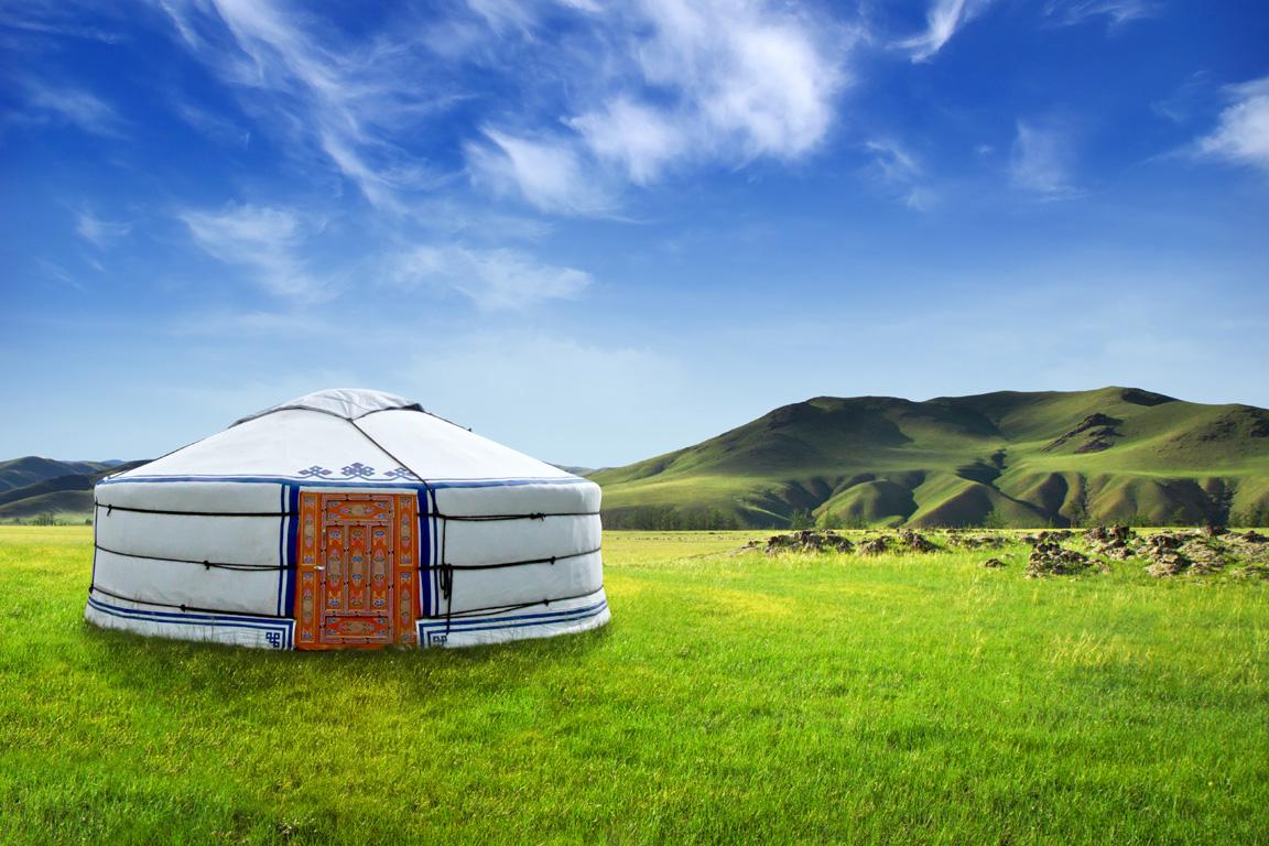 yurt in a green field under a blue sky